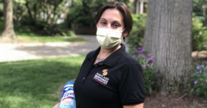 "Woman wearing a surgical mask, ""Maryland Responds"" polo shirt and holding a canister of wipes"